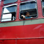 A boy peers out a bus window in Mumbai, India. Photo by gregor_y.